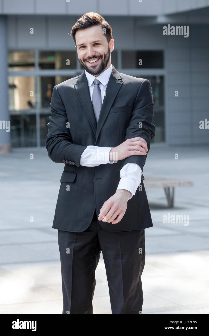 Portrait of business man adjusting cuffs - Stock Image