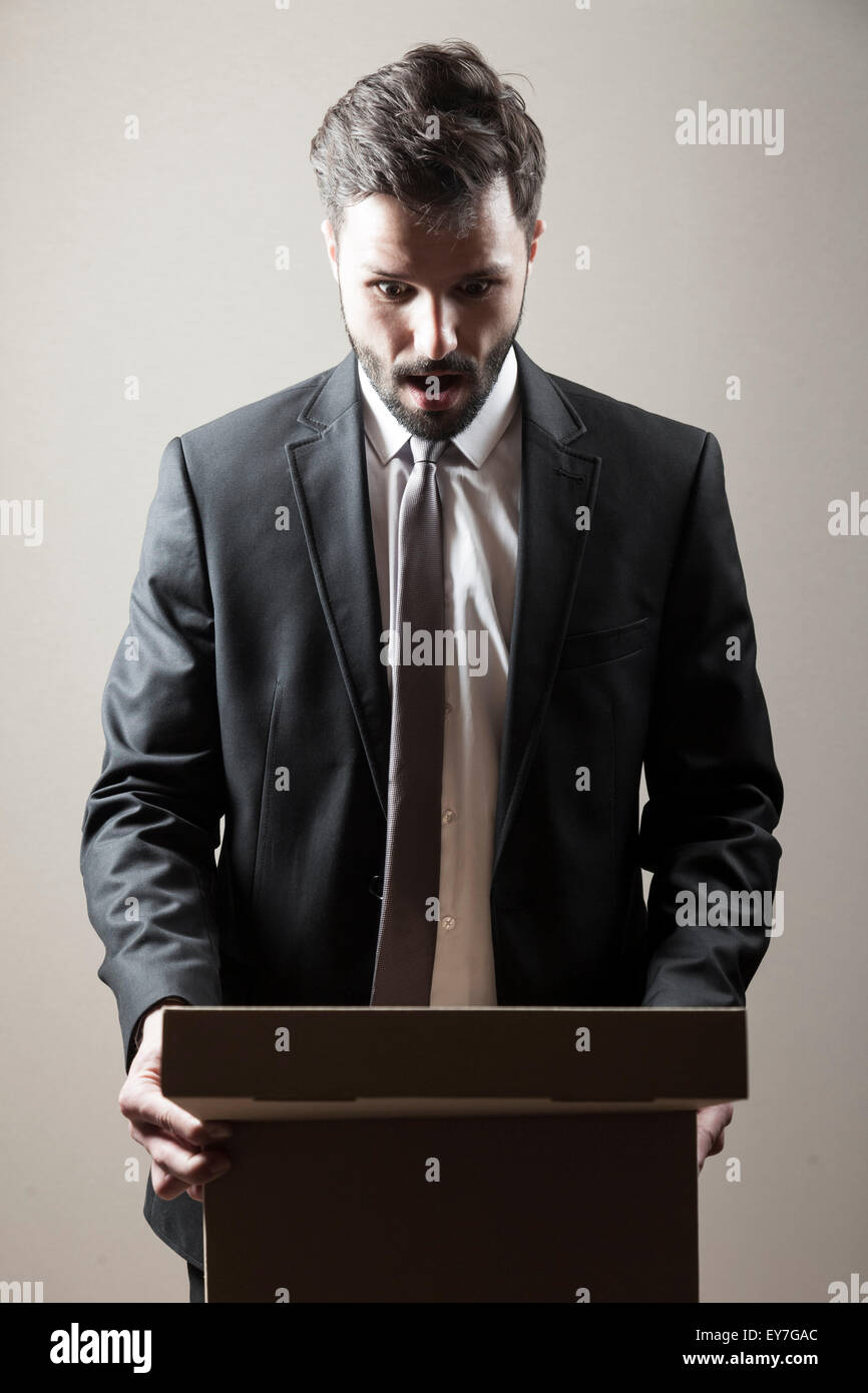 Businessman looking at cardboard box mouth open - Stock Image