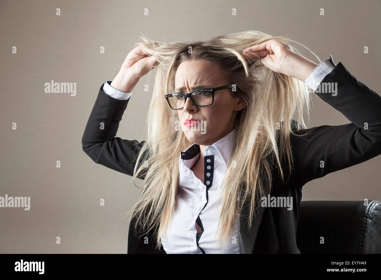 Businesswoman pulling her blond hair - Stock Image