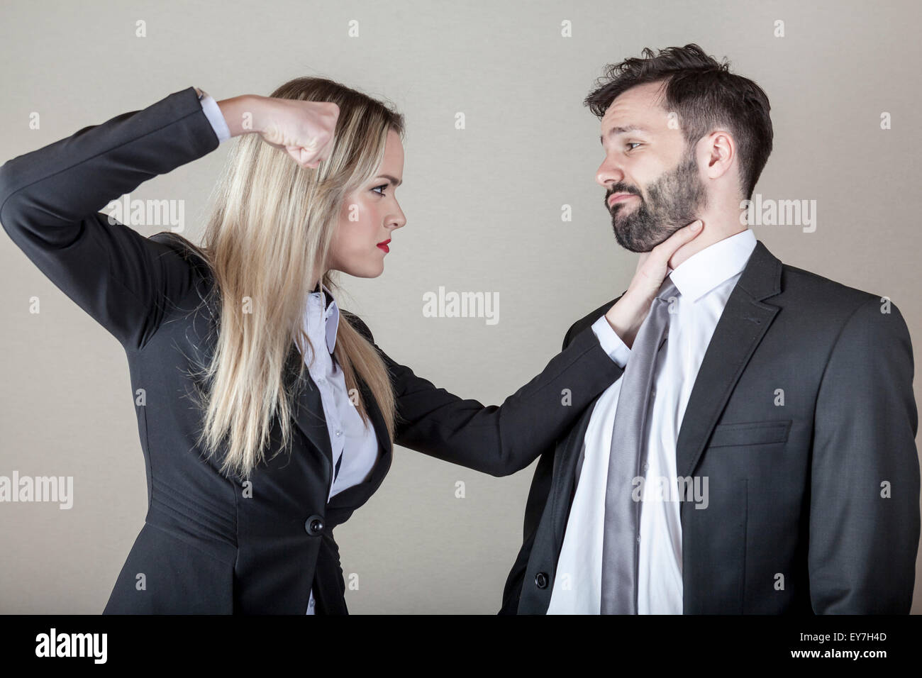 Business woman strangling a business man - Stock Image