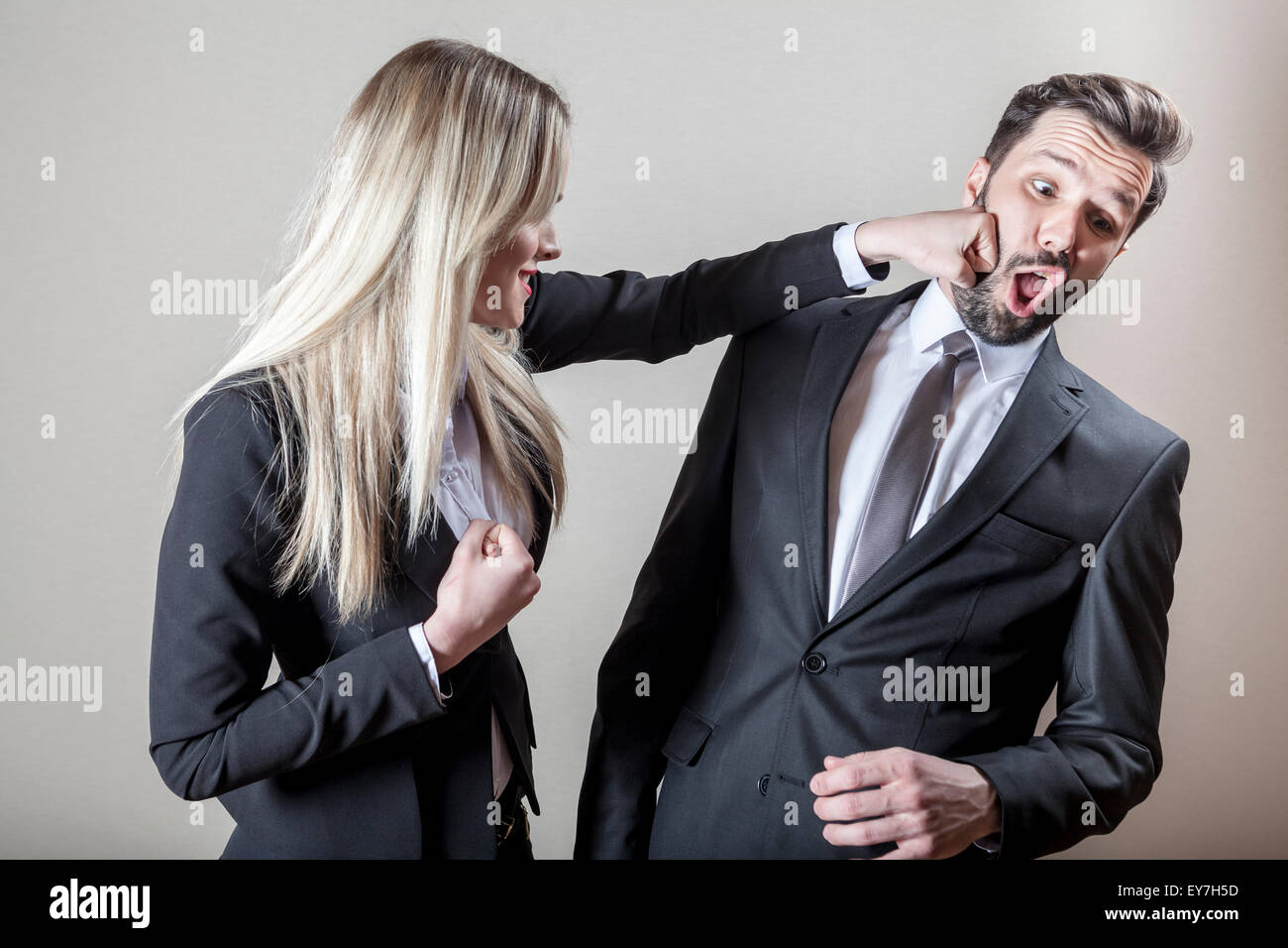 Businesswoman hitting businessman with fist - Stock Image
