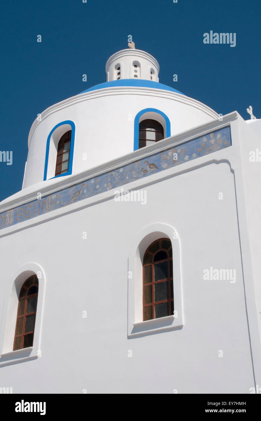 White churches often decorated with blue roofs are favored for touristic photos in Oia an Santorini Island. - Stock Image