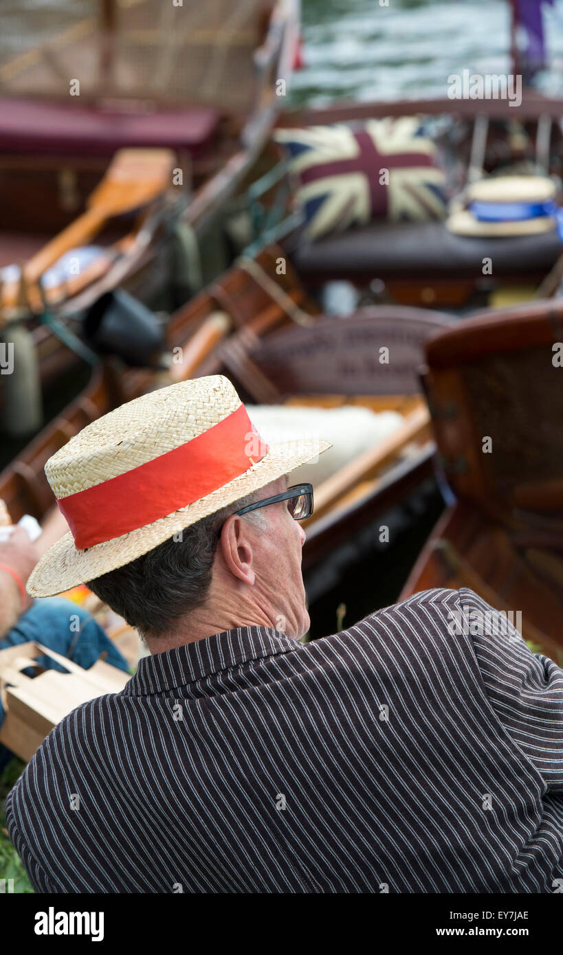 Man in a striped jacket and straw boater watching the boats at the Thames Traditional Boat Festival, Henley On Thames, - Stock Image