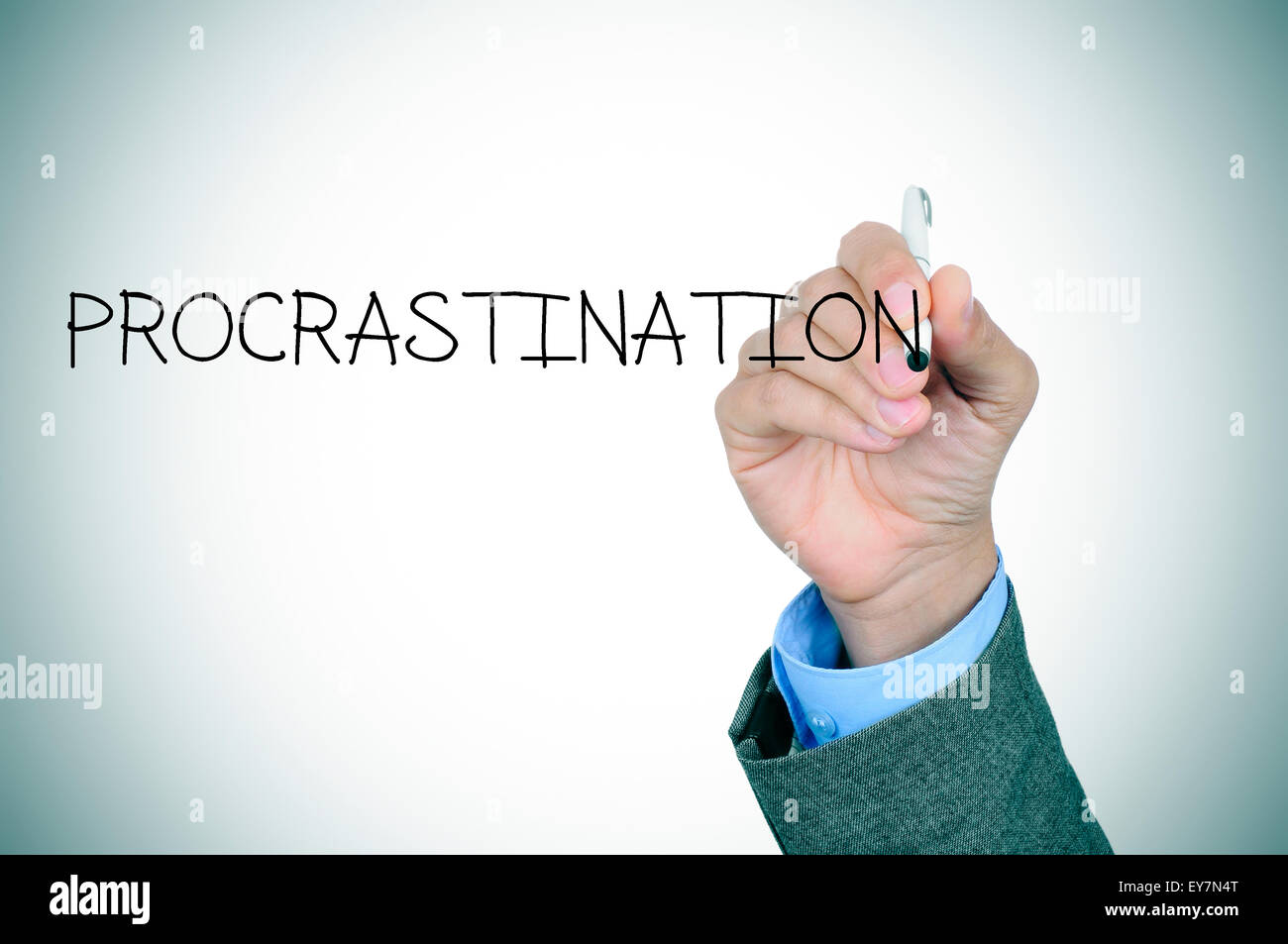 closeup of the hand of a man writing the word procrastination in the foreground - Stock Image