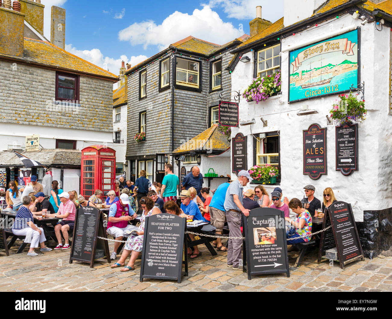 People sitting outside the historic Sloop in on the seafront, Wharf Road, St Ives, Cornwall, England, UK - Stock Image