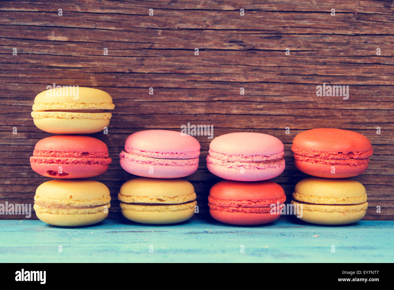 some appetizing macarons with different colors and flavors on a blue rustic wooden surface, cross processed - Stock Image