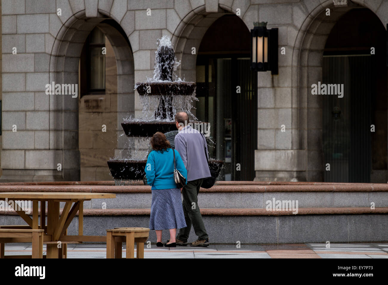Well dressed middle aged couple standing admiring the water fountain at the City Square in Dundee, UK - Stock Image