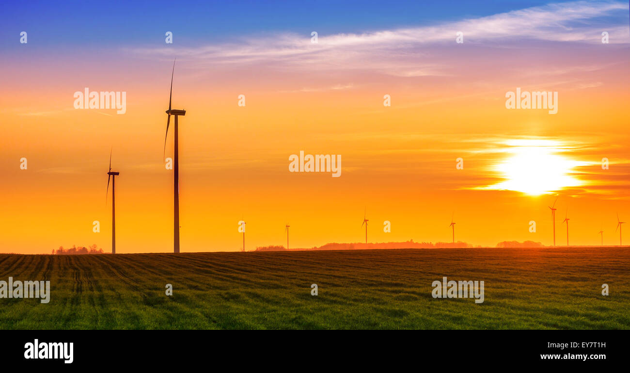 Renewable energy concept, windmills at sunset. Stock Photo
