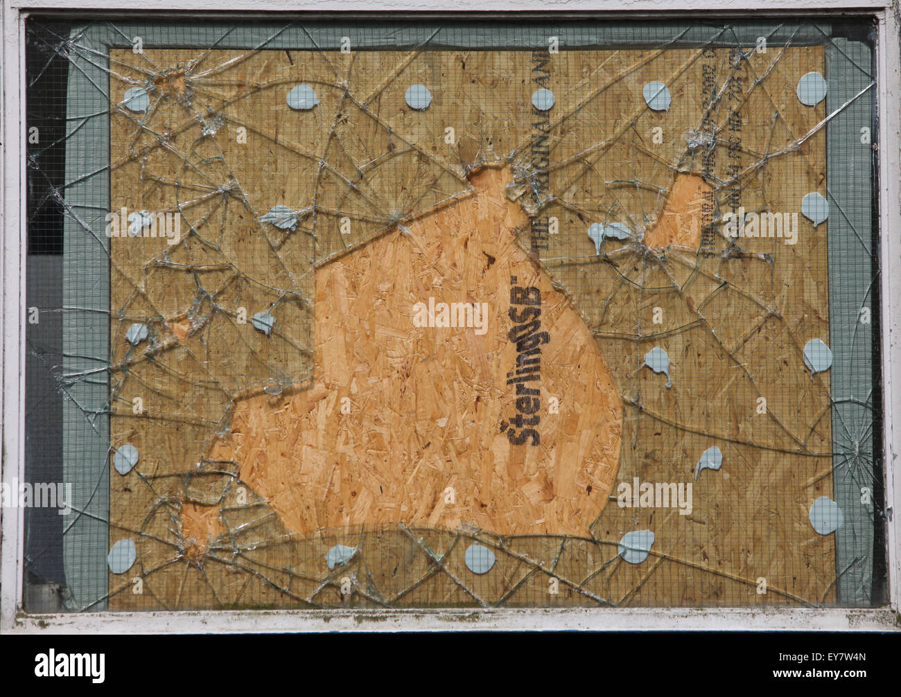 A smashed window repaired with a wooden panel - Stock Image