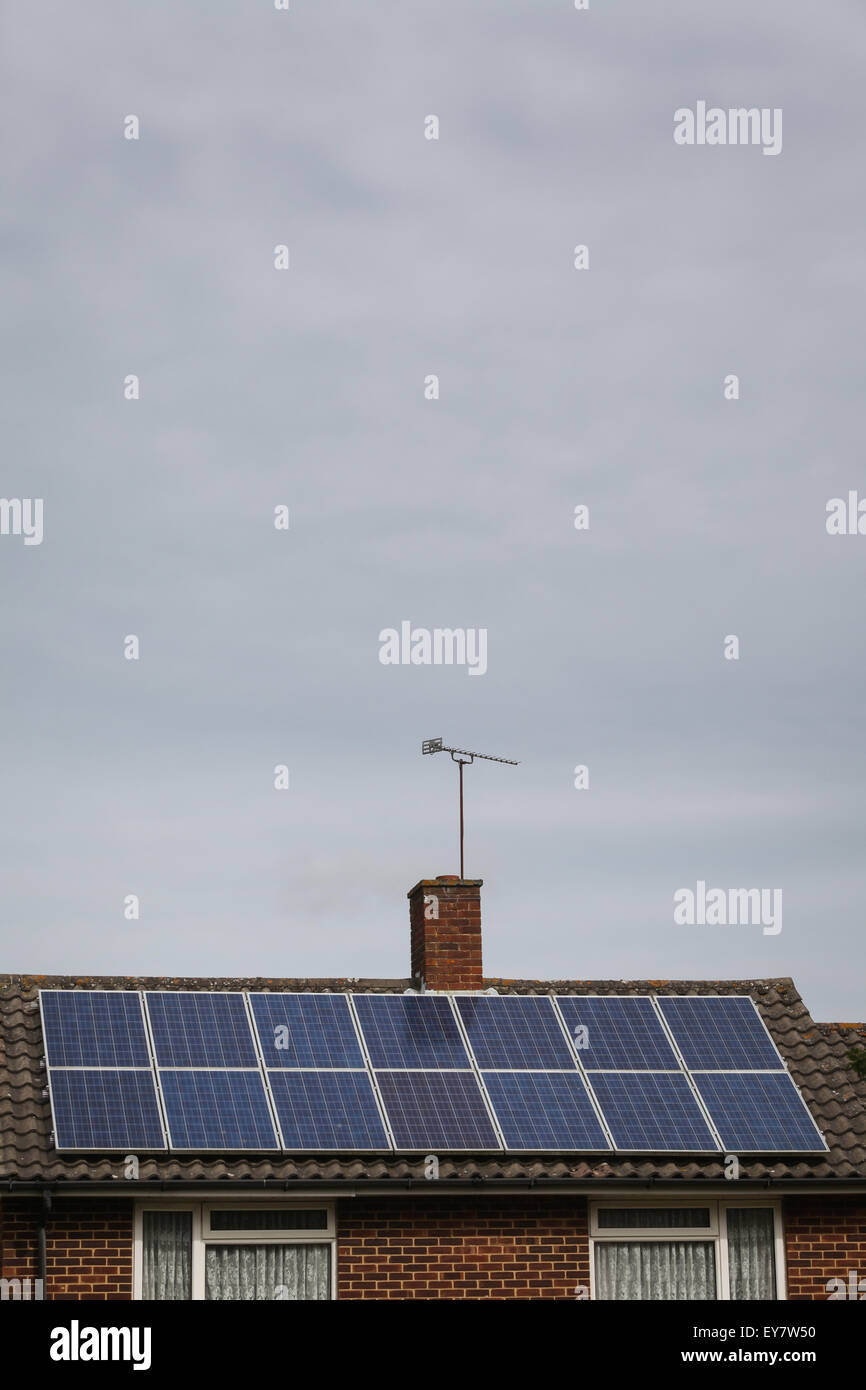 Solar panels on the roof of a house on a grey overcast day not generating much energy - Stock Image