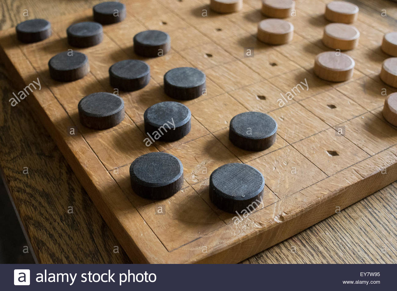 A wooden draughts board and pieces resting on a wooden table - Stock Image