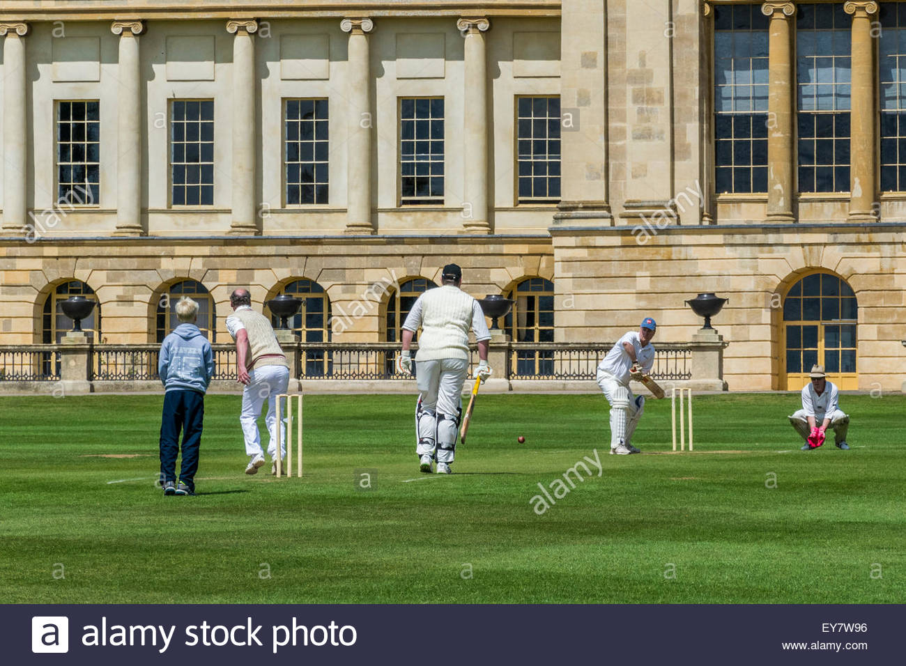 Batsman faces the bowler in a cricket match with the stately home of Stowe House in the background - Stock Image