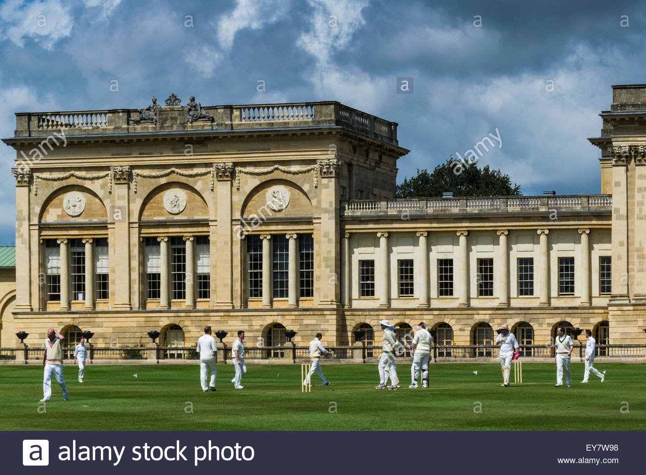 Cricketers in a cricket match with the stately home of Stowe House in the background - Stock Image