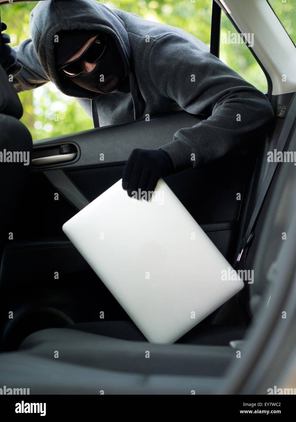 Car theft - a laptop being stolen through the window of an unoccupied car. - Stock Image