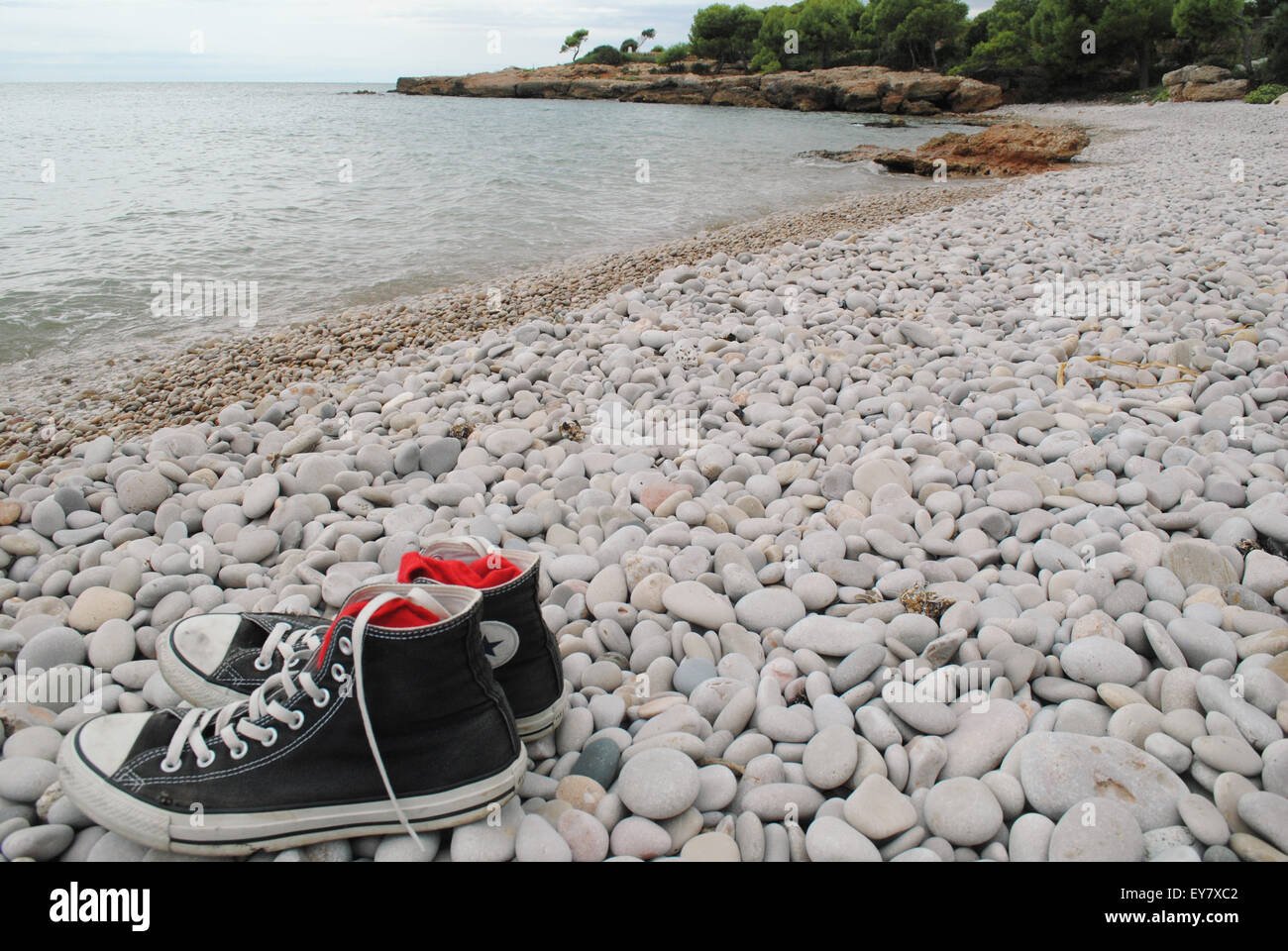 A pair of high top sneakers on a pebble beach in cloudy weather. Stock Photo
