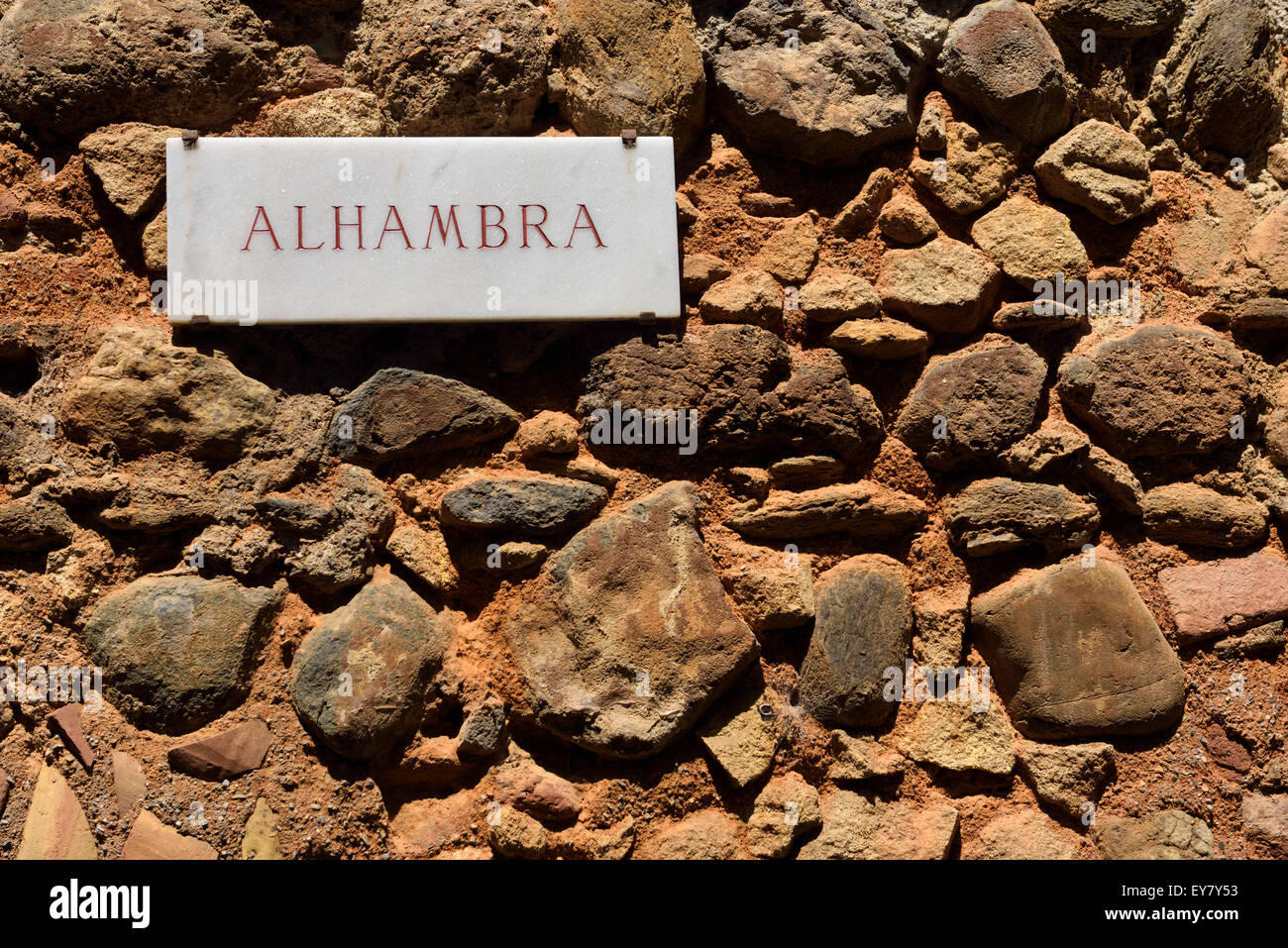 Sign for Alhambra at Gate of Justice on the ancient fortified wall of the hilltop fortress in Granada - Stock Image