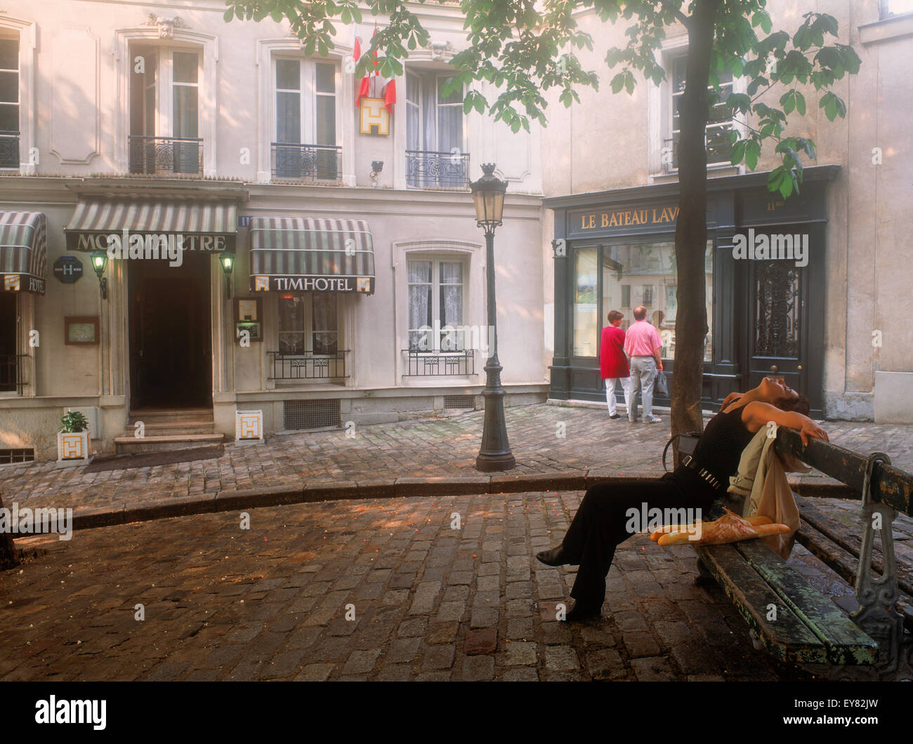 Parisian woman with baguette resting in small quiet Montmartre square - Stock Image