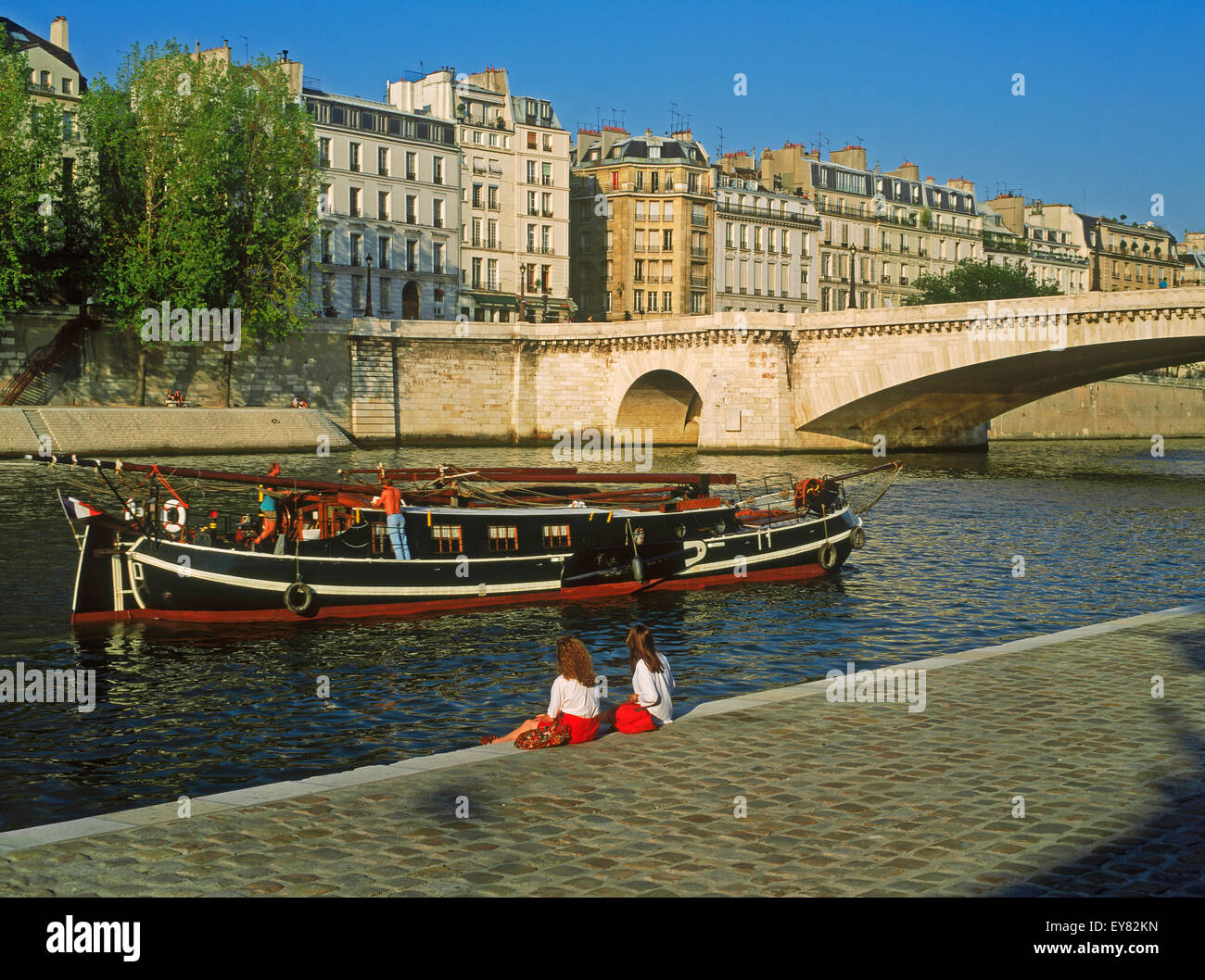 Two women relaxing near Ile St Louis on River Seine with boat passing below apartment buildings in Paris - Stock Image