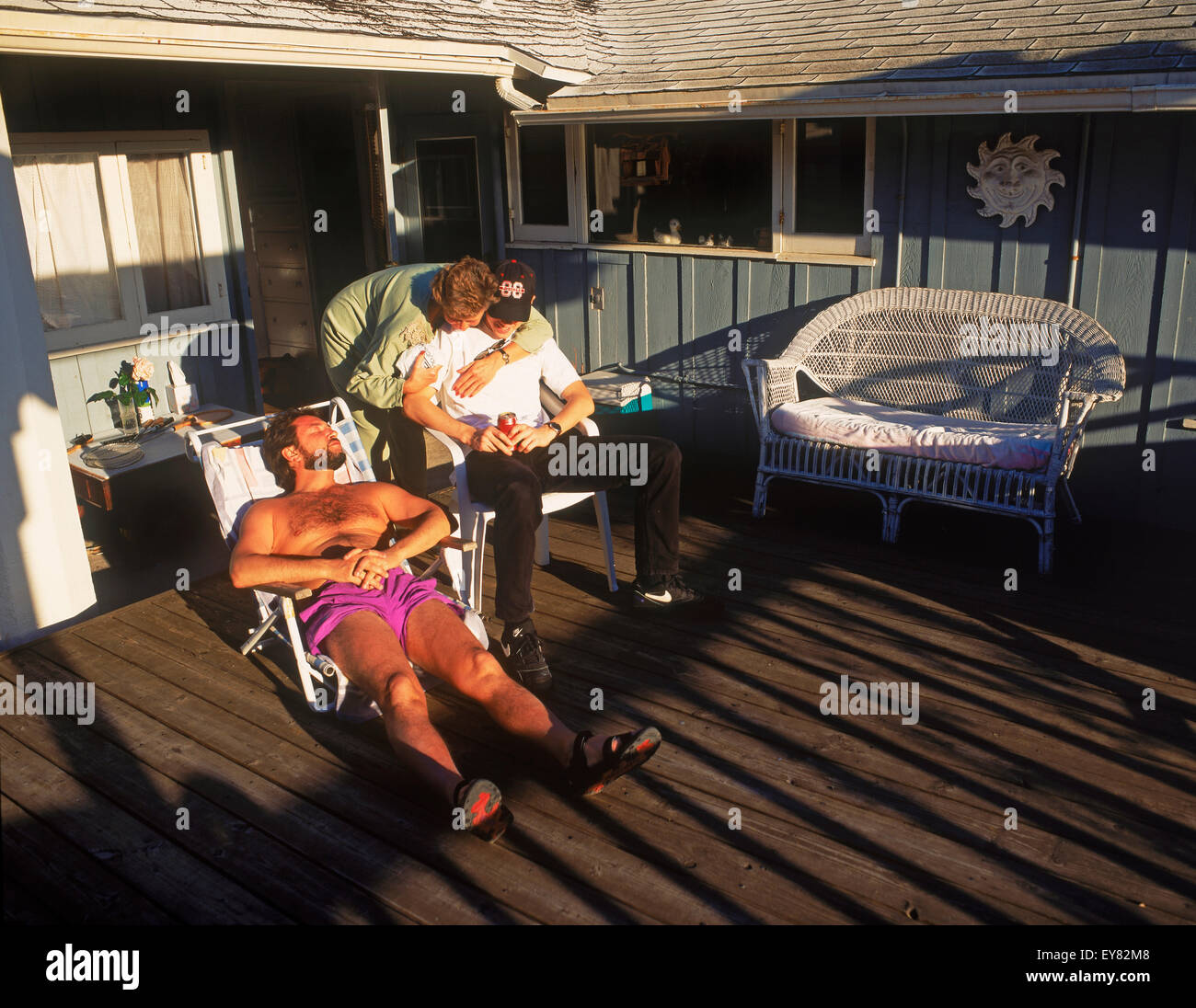 Coastal homes and sun bathers at Woods Cove in Laguna Beach on a warm winter day in  Southern California sunbathing - Stock Image