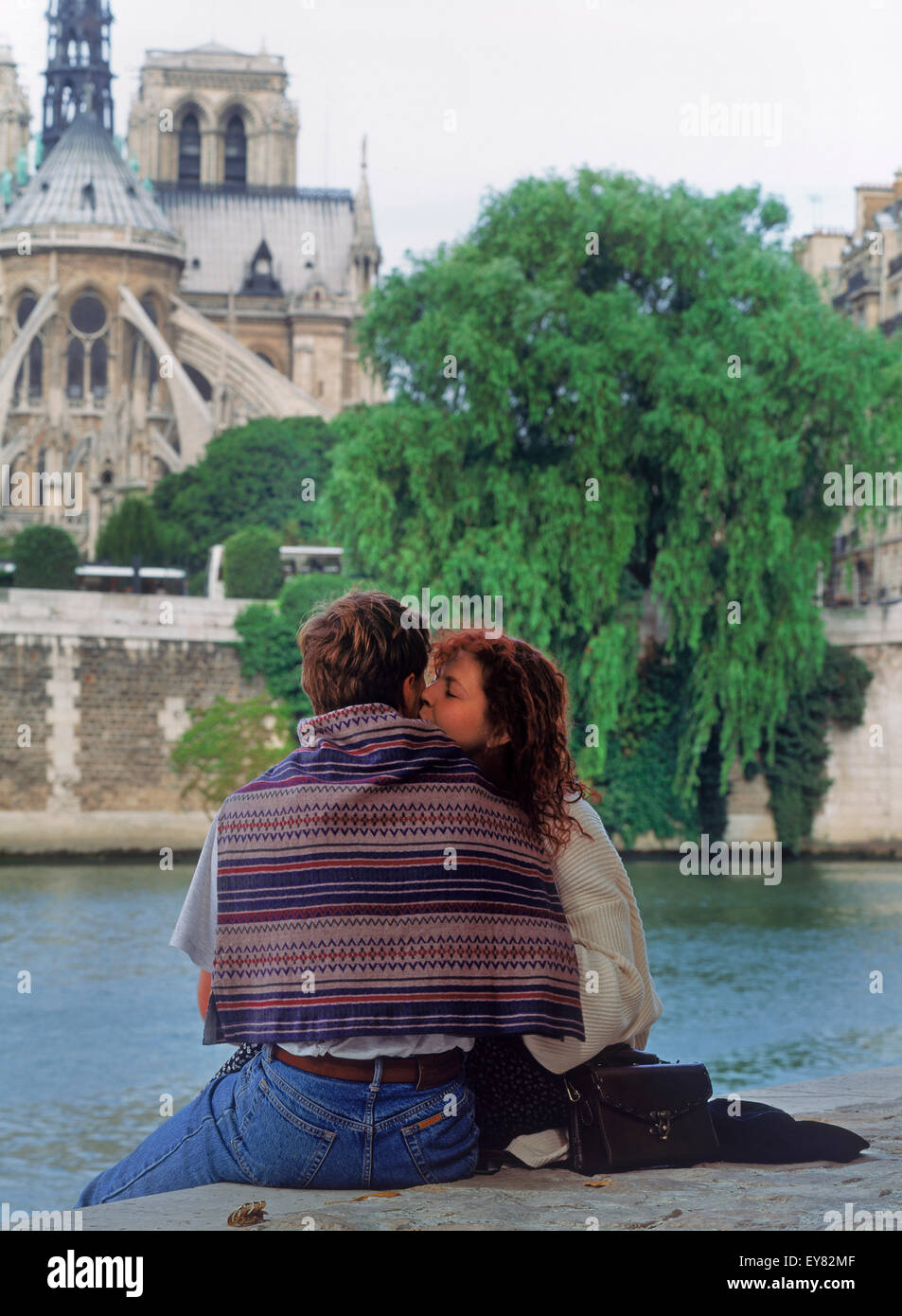 Couple kissing at Ile St Louis on River Seine across from Notre Dame in Paris - Stock Image