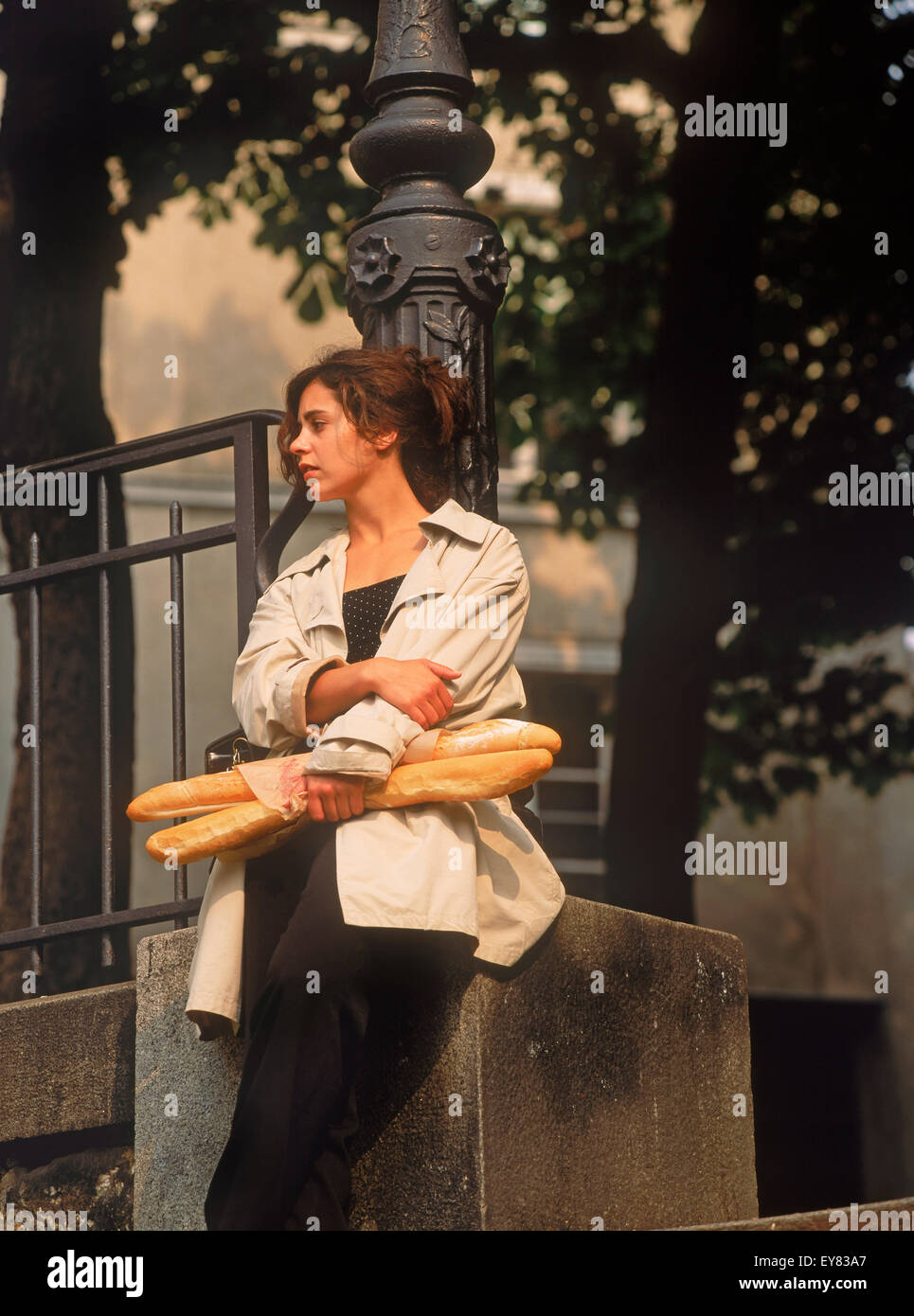 Parisian woman with baguettes resting against street lamp post in quiet Montmartre square - Stock Image