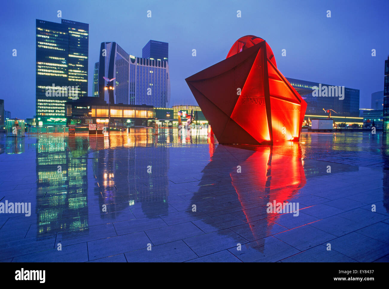 The Arch and modern sculptures at La Defense reflecting of wet surface on rainy night - Stock Image