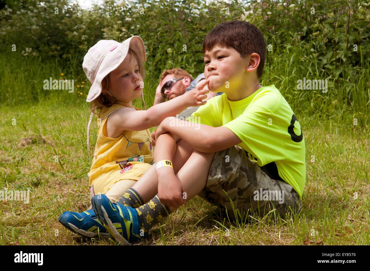 Little girl putting suncream on boys face - Stock Image