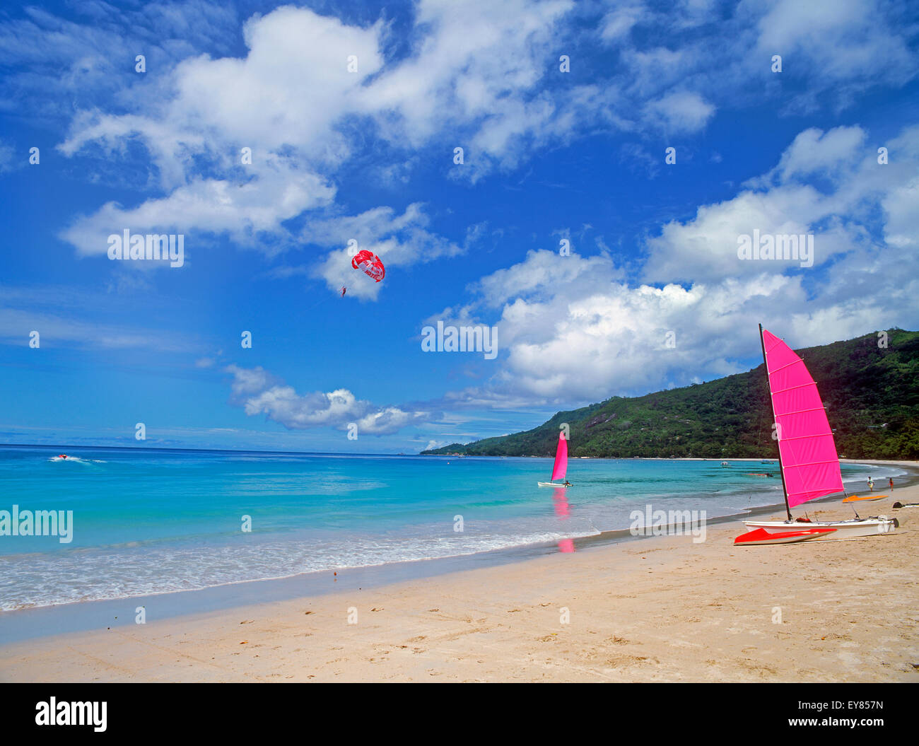 Catamaran on sandy shore beach and on the water under parasailor on Mahe Island in the Seychelles - Stock Image
