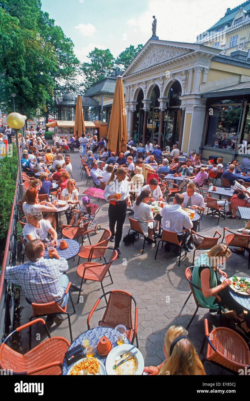 Summer tourists and activities around outdoor sidewalk restaurants near South Harbor in Helsinki, Finland - Stock Image