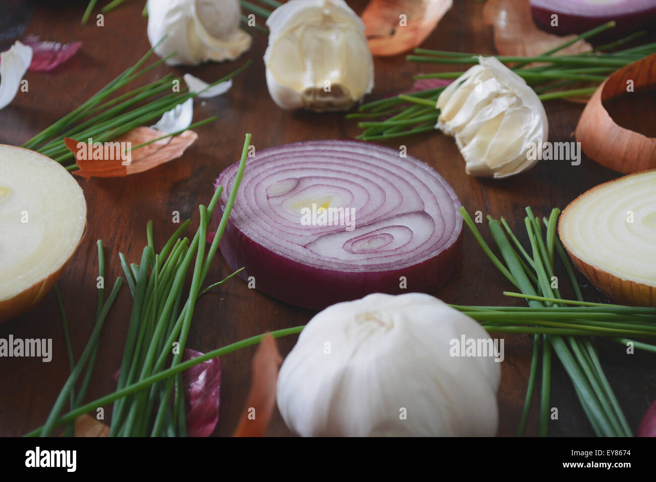 Onions, chives and garlic scattered on wood table for food preparation and cooking concept, with applied retro vintage - Stock Image
