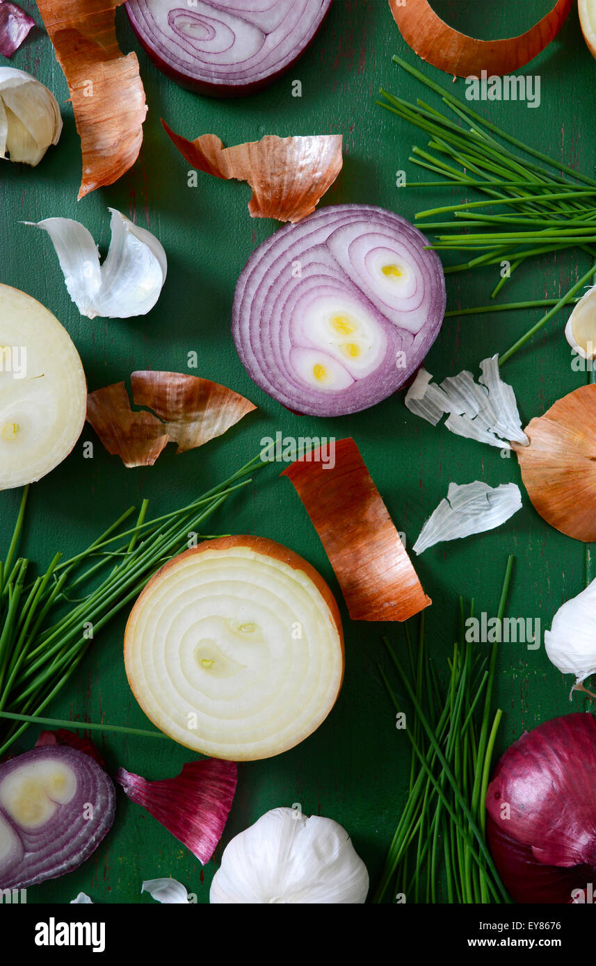 Onions, chives and garlic scattered on old green wood table for food preparation and cooking concept. - Stock Image
