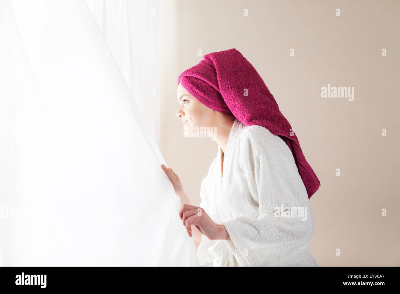 Young woman in bathrobe looking out of window - Stock Image