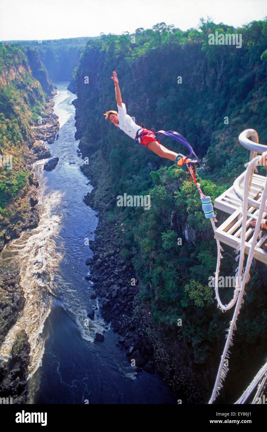 Bungy or bungee jumping off 152 meter high Victoria Falls Bridge above Zambezi River between Zimbabwe and Zambia - Stock Image