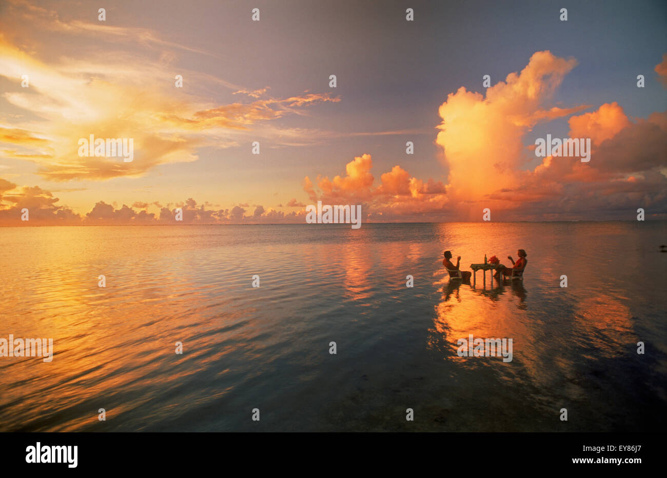 Couple sitting at table sharing sunset drink in lagoon in middle of the Pacific Ocean. Holiday serenity and solitude - Stock Image