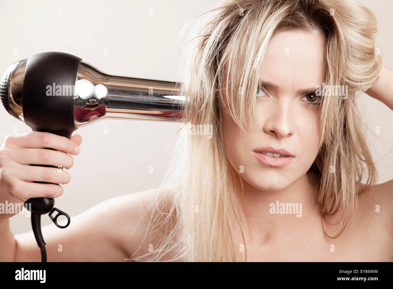 Young woman drying her hair - Stock Image