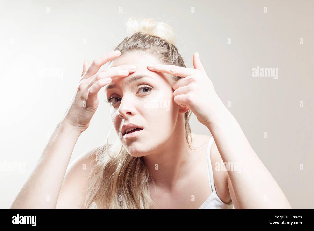Young woman examining face - Stock Image