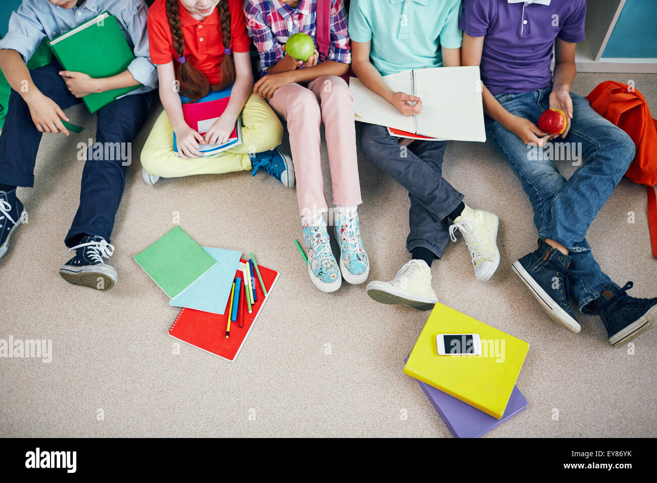 Group of schoolmates in casualwear sitting on the floor - Stock Image
