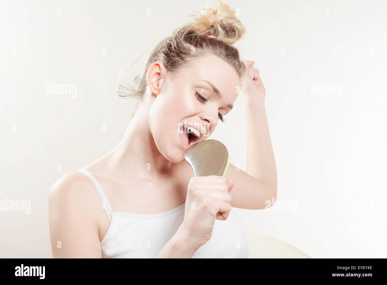 Young woman singing into hairbrush - Stock Image