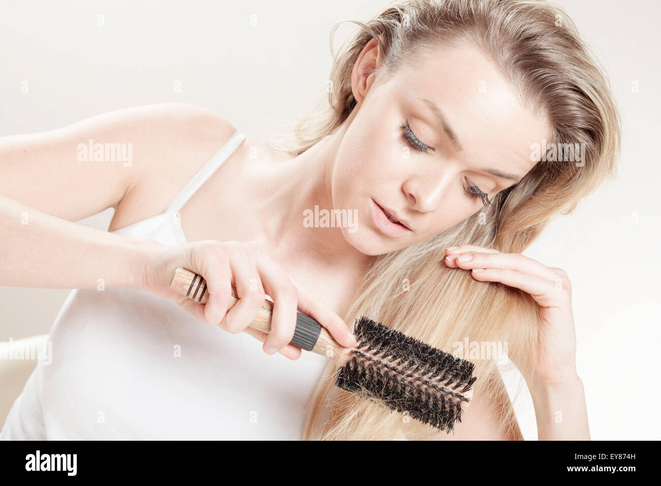 Young woman brushing her hair - Stock Image