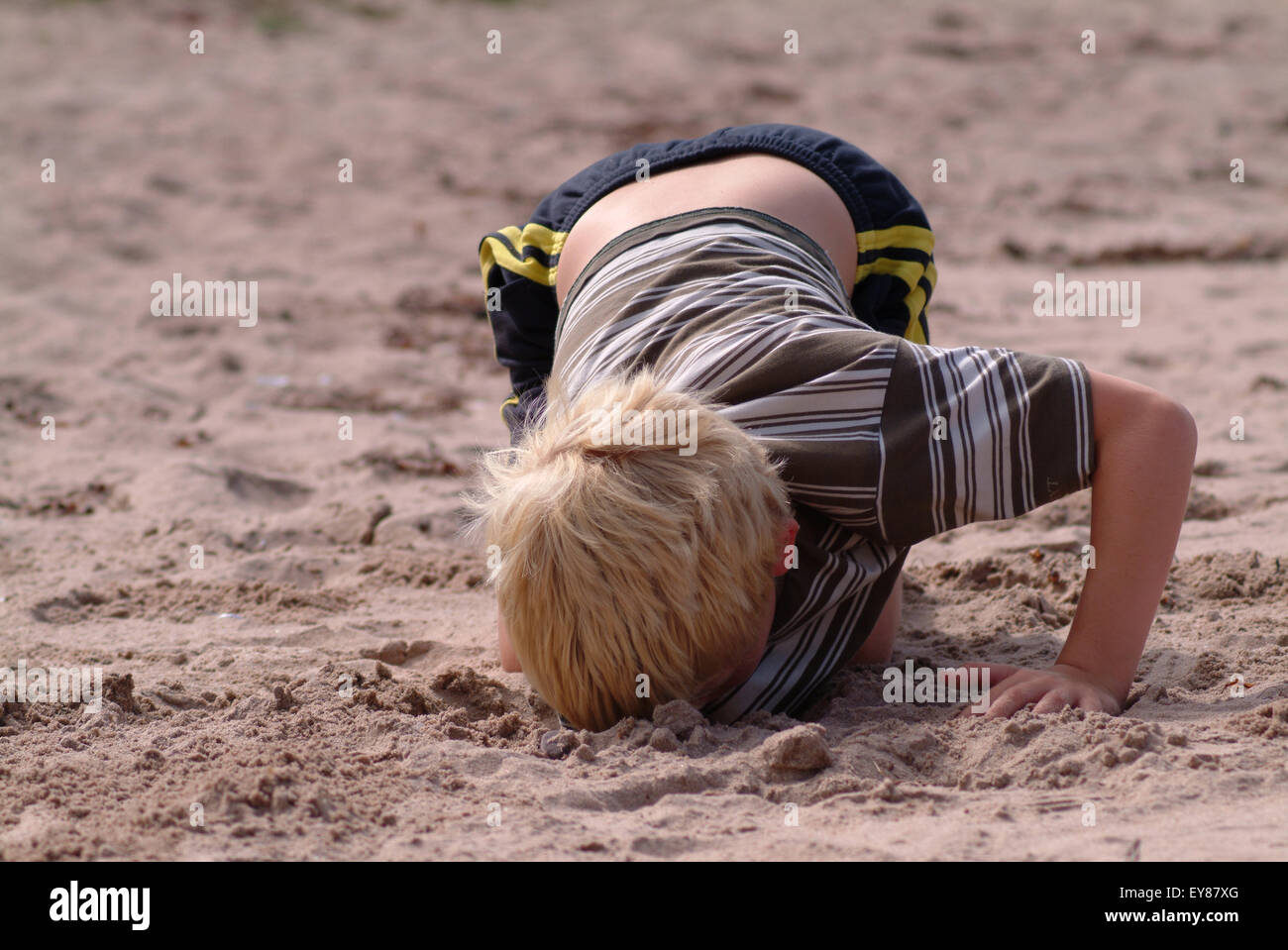 Blonde haired boy digging a deep hole in the sand - Stock Image