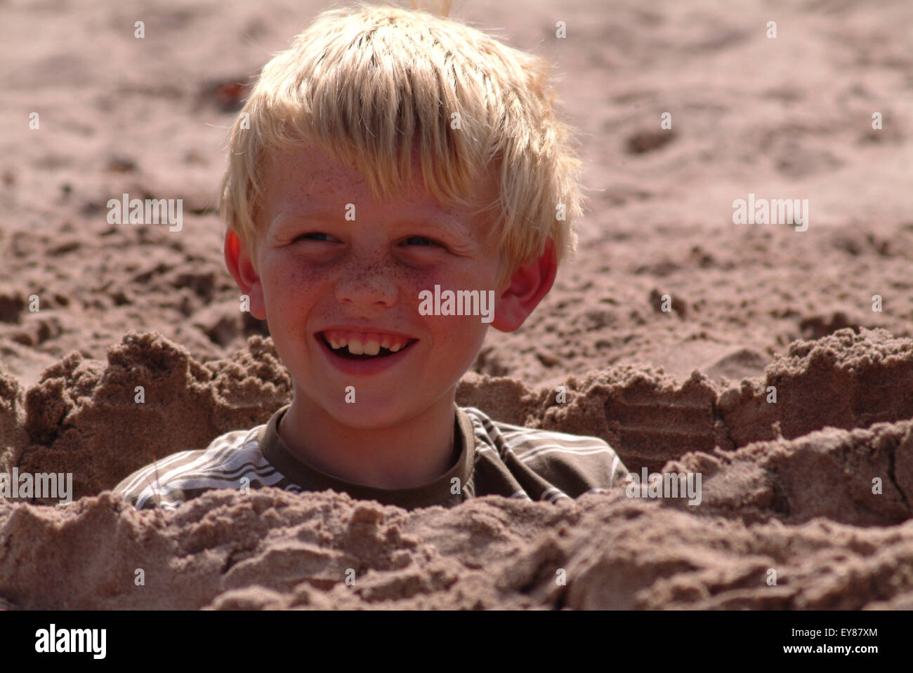 Blonde haired boy with freckles, smiling, laughing, sitting in a sand hole - Stock Image
