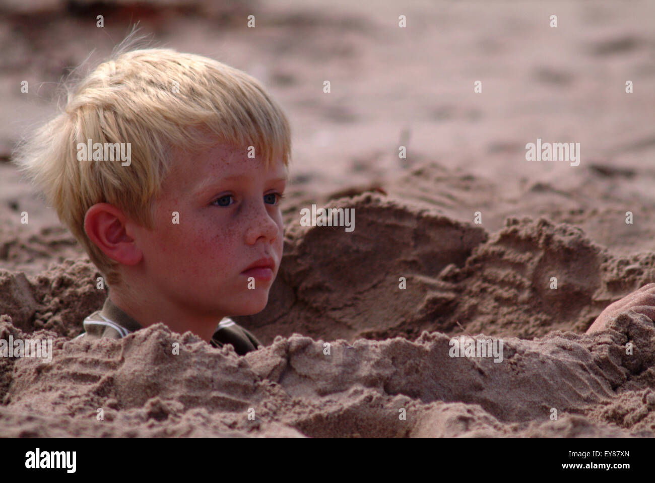 Blonde haired boy looking pensive, sitting in a deep sand hole - Stock Image