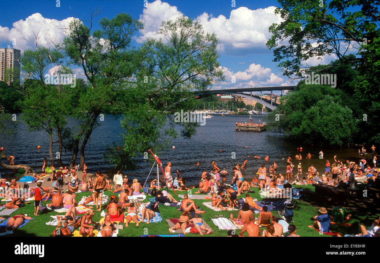 Summer sunbathers at Langholmen Island in Stockholm on Riddarfjarden waters - Stock Image