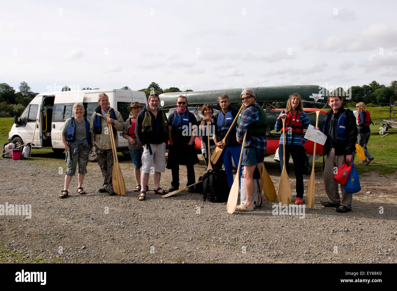 Group of people about to go canoeing, posing for a photograph - Stock Image