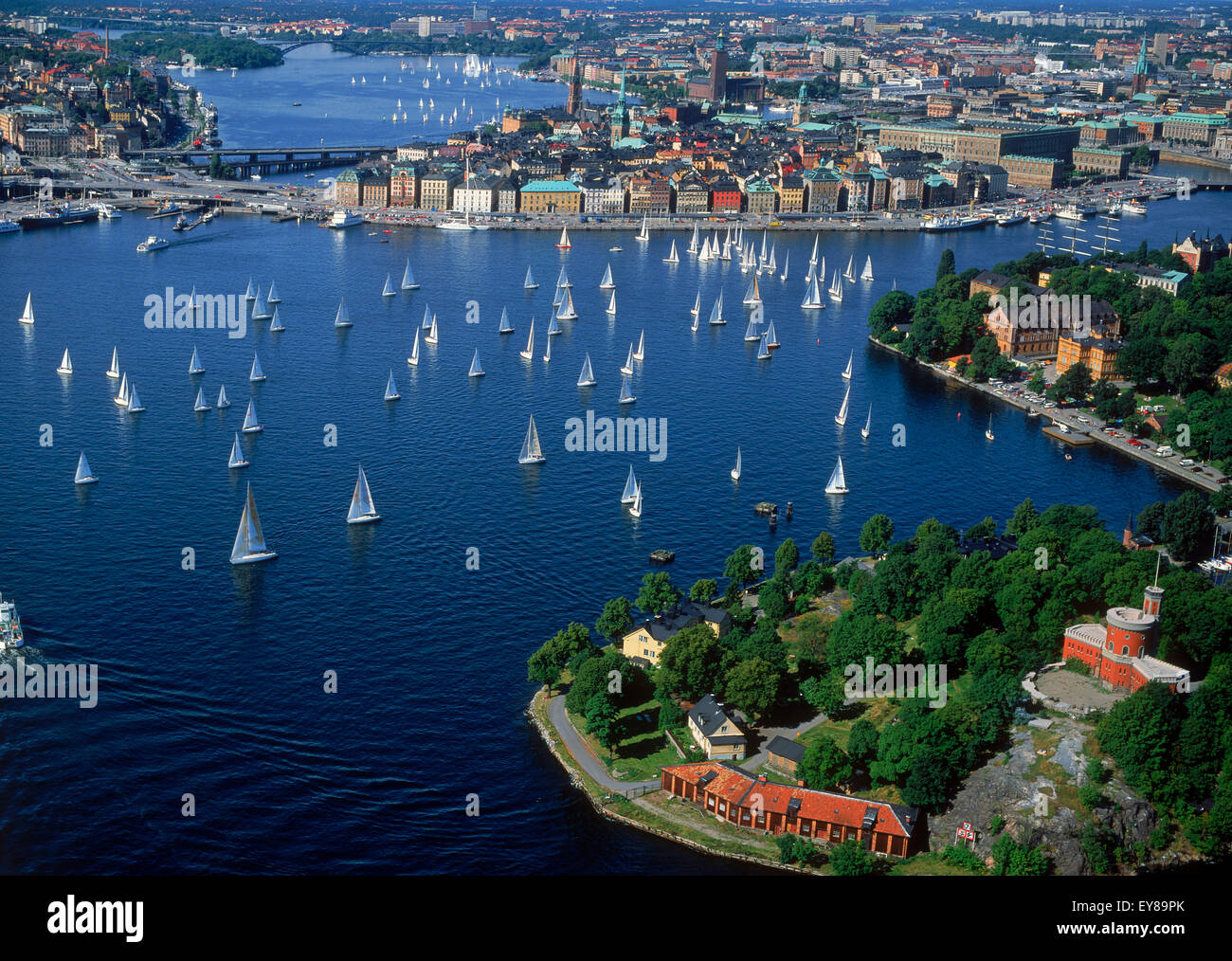 Aerial view of sailboats surrounding The Old Town of Stockholm during summer regatta on Saltsjön waters a bay - Stock Image