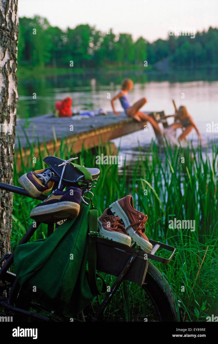 Two girls enjoying summer swim from lakeside dock  in Sweden - Stock Image