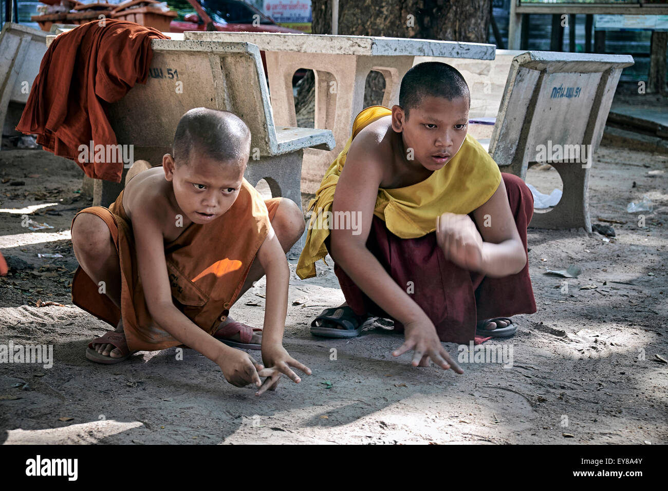 Young boy Buddhist monks playing traditional marbles game. Thailand S. E. Asia - Stock Image