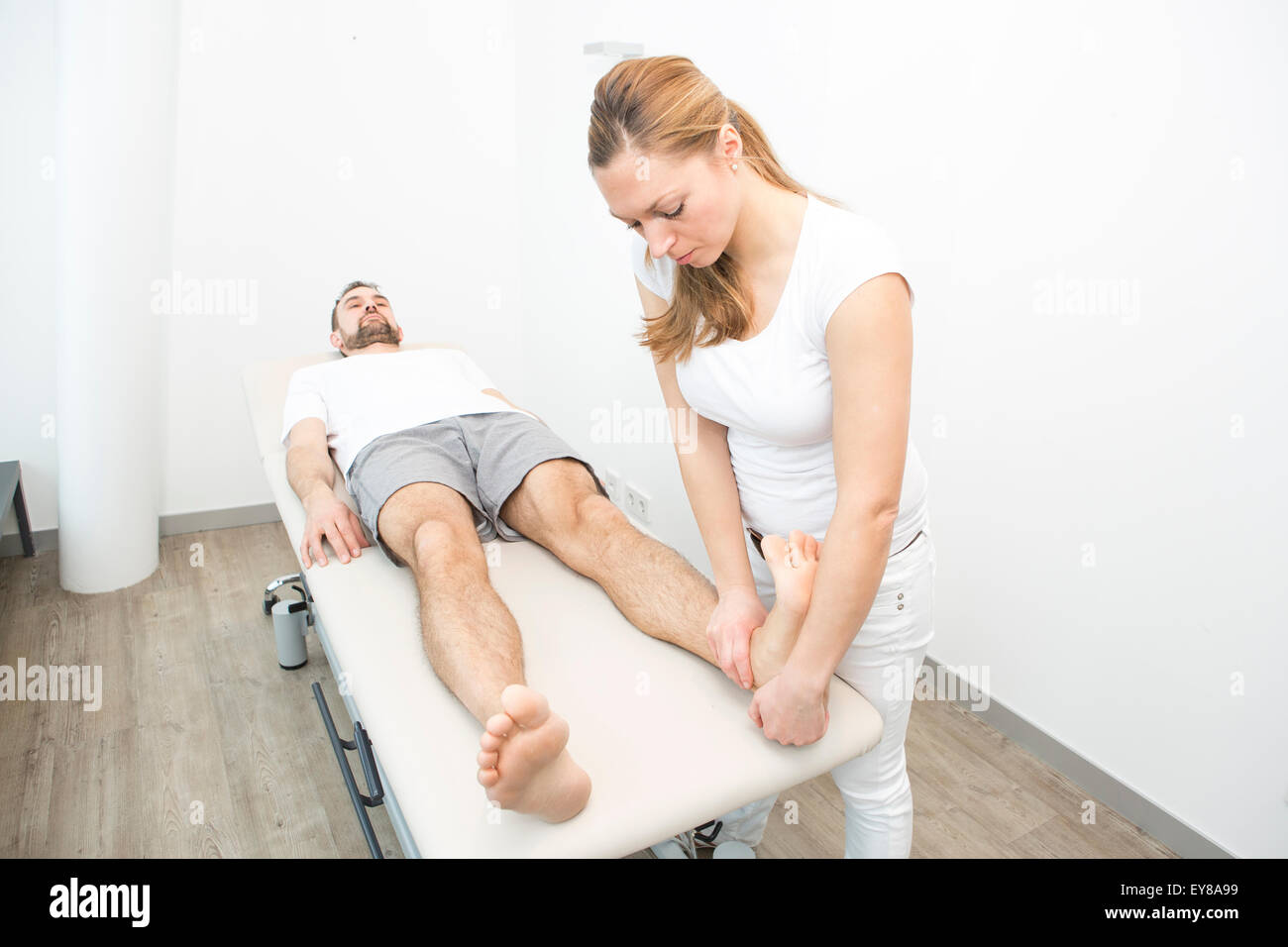 Physiotherapist helping patient to do leg exercise Stock Photo