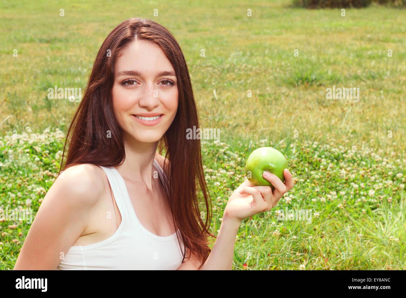 Nice young girl eating apple - Stock Image