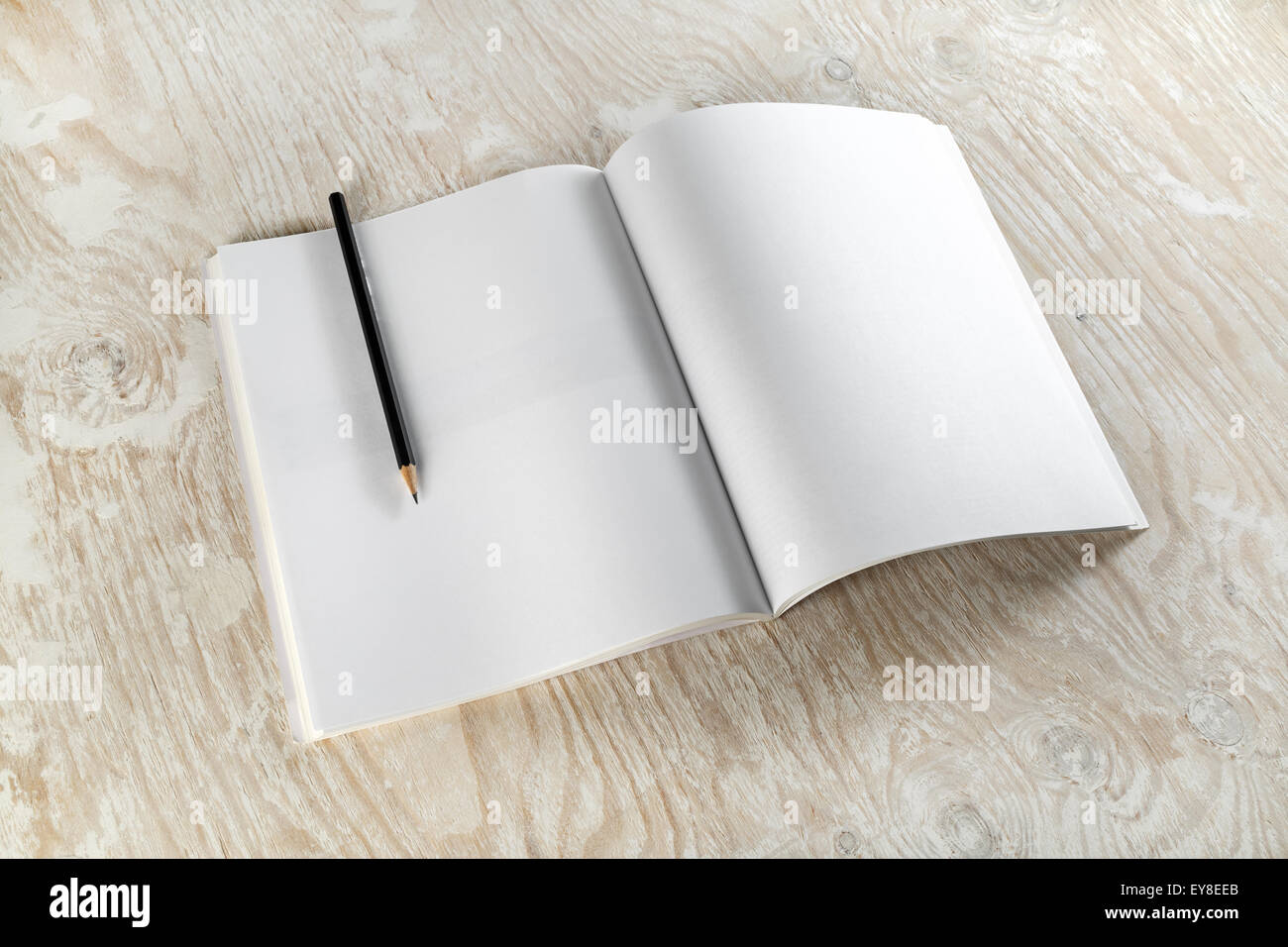 blank opened brochure with a pencil on light wooden background with